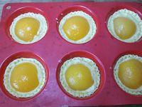 3 - Ressortir le moule du réfrigérateur et déposer dans le fond de chaque tartelette une bonne couche de crème à la noisette. Venir installer au centre un oreillon d'abricot en appuyant dessus pour l'enfoncer un peu dans la crème. Mettre à cuire au four th 6 (180°) pendant 20 à 25 mn en surveillant. Sortir du four, laisser refroidir complètement. Disposer les tartelettes sur un plat de service, protéger les oreillons d'abricot à l'aide de disques découpés dans du papier absorbant (ou autre) et saupoudrer bien l'ensemble de sucre glace. Retirer le papier et répartir au pinceau sur les oreillons un peu de confiture d'abricot diluée avec un peu d'eau. Vos gourmandises sont prêtes à être dégustées.