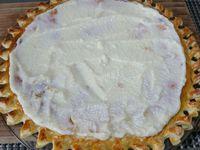 1 - Mettre le four à préchauffer th 6 (180°). Laver et sécher les fruits frais. Etaler la pâte feuilletée. Faire des incisions au couteau dans les bords de la pâte et entrecroiser les petites bandes ainsi réalisées. Dorer les bords de la tarte au pinceau avec un jaune d'oeuf délayé dans un peu d'eau et piquer le fond à l'aide d'une fourchette. Mettre au four th 6 (180°) pour une cuisson à blanc pour 12 à 15 mn environ en surveillant. Pendant ce temps préparer une crème pâtissière (voir lien ci-dessous pour la réalisation de la crème pâtissière) ou utiliser une crème congelée préparée à l'avance. Sortir la tarte du four après cuisson et laisser refroidir. Tailler les fraises et les pêches en lamelles et en quartiers. Garnir la pâte refroidie d'une couche de crème pâtissière (à température ambiante) et venir y disposer joliment tous les fruits en les alternant. Parsemer d'un peu de verveine citron hachée, et décorer le centre de la tarte de quelques feuilles de verveine entières. Déguster en dessert à la fin d'un repas ou au goûter.
