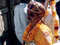 Dahinter folgten einige alte Männer. Um diesen Herren ging es wohl. Vor ihm wurden weiße Tücher ausgebreitet wie ein roter Teppich. Viele Zuschauer kamen zu ihm, knieten sich vor ihm nieder, berührten seine Füße, falteten dann ihre Hände vor ihrem Kopf und hingen ihm Blumenkränze um. Daminter liefen viele blumengeschmückte Frauen in bunten Saris.