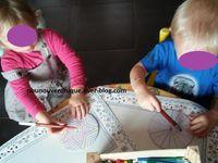 Tracer un cercle sur un carton puis le découper. Tracer des formes géométriques avec des feutres, puis laisser l'enfant décorer aux feutres ou avec des gomettes. Passer un élastique fin au centre du carton à l'aide de l'aiguille.