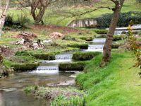 Du chemin, sur la colline, on aperçoit l'orangerie et l'étang, au loin le village de Sasnières. Le pont de bois et la cascade d'eau claire