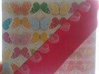 Voici un marque page avec des papillons collés en relief et un ruban rose et des petits rubans transparents.