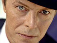 """David Bowie, debout devant une porte de garage. Est-ce que cela signifie qu'il est mis """"au garage"""", gardé de côté pour plus tard? >Fait étrange, il porte un chapeau, couvre chef dont Roch Sauquere pense que s'affublent les voyageurs du temps ( trait commun aux MIB, men in blacks). En plus ce chapeau en particulier ressemble à celui porté par Roch dans une photo noir et blanc utilisé pour encourager les lecteurs à un concours """"photos insolites""""...Bowie avait un oeil gauche différent du droit, soit disant à cause d'une coup de poing lors d'une bagarre d'enfance. Troublant tout de même, lorsque l'on sait que l'œil gauche est attribué à Satan. Les personnes sous contrôle mental/possession démoniaque, ont leur œil gauche affaissé..."""