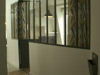 L'architecte a conçu cette verrière pour créer de la lumière, la cliente souhaitait pouvoir moduler la lumière selon ses besoins. Céline Quémat a sélectionné ce tissu et  réalisé ce rideau double face sur mesure. L'ourlet et la tête du rideau sont invisibles pour être vu des deux côtés. Du côté du couloir le rideau est dans un tissu art-déco pour apporter une touche décorative. Du côté de la pièce le rideau est dans le tissu des stores