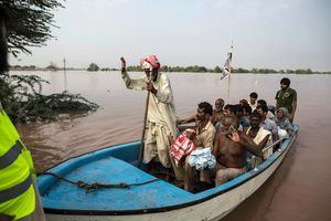 Pakistan Floods - A flood victim reacts as he arrives on dry land