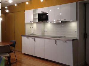 Vues sur cuisine, coin repas et salon. Les cloisons vitrées en serrurerie laissent passer la lumière dans tout l'appartement. Des rideaux occultants permettent cependant d'isoler les chambres du salon.