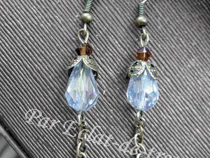 BOUCLES D'OREILLES BRONZE LARME CRISTAL - Boucles d'oreilles composées de deux calottes en forme de fleur et de deux perles en forme de larme. Les cristaux d'Autriche sont de couleur marron.  Longueur : 6cm. PRIX : 12.50 EUROS