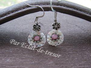 BOUCLES D'OREILLES TISSÉES MARGUERITE PERLE MAGIQUE ROSE - Jolies boucles d'oreilles décorées d'une perle nacre en forme de coeur et tissées de perles japonaises et d'une perle magique de couleur rose aux multiples reflets. Nous retrouvons des couleurs discrètes dans les perles qui composent ce bijou : rose, blanc, gris... Longueur : Environ 4 cm. Diamètre : 12 mm. Note : Livrées dans leur pochette en organza. PRIX : 14 EUROS