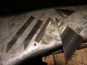 La plaque d'or ramenee de 10/10 a 7/10 mm au laminoir&#x3B; le triangle, et dans la chute trois bandes, sont decoupes. Il reste un petit triangle qui me servira a la fin.