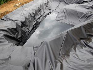 remplissage du bassin avec de l'eau de pluie puis tirage sur l'epdm pour éviter un maximum de pli mais dans tout les cas il en restera, encore plus si votre bassin contient des arrondies