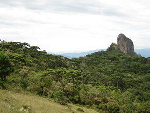 au détour d'un virage sur la piste d'accès au départ de la randonnée pédestre, on découvre enfin le panorama. Tout d'abord les trois rochers en enfilade : le plus imposant c'est Pedra do Bau, mais juste devant lui, presque éclipsé par la végétation sur cette face Est on voit Bauzinho, et derrière Bauzinho, à sa droite, on devine Ana Chata, rendu minuscule par la perspective.