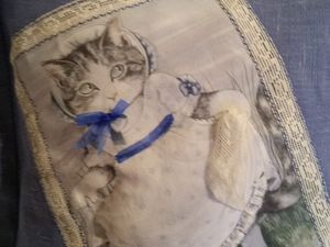 en lin bleu lavande,la precieuse petite chatte est imprimée sur du lin blancet egalement reprise en relief,entourée d'une dentelle ancienne .