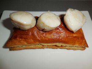 4 - Mettre le reste de beurre dans une poêle, faire revenir les noix de St jacques 1 mn sur chaque face, les poser sur du papier absorbant pour ôter le surplus de gras et réserver au chaud. Découper vos rectangles de pâte feuilletée sortis du four dans le sens de la longueur. Les remplir de préparation poireaux/champignons, recouvrir . Déposer chaque feuilleté dans une assiette de service, disposer 3 à 4 noix de St Jacques sur chaque feuilleté, saupoudrer de piment doux . Rajouter sur le plat la crème d'ail chaude, et éventuellement agrémenter de quelques feuilles de salade.