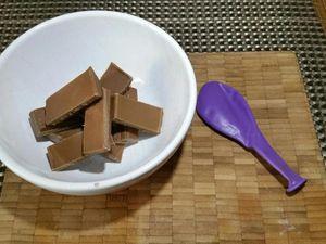 2 - Faire fondre le chocolat avec précaution au micro-ondes dans un bol. Laisser légèrement tiédir. Gonfler un ballon à la taille voulue et en tremper la base délicatement dans le bol de chocolat. Poser un petit disque de chocolat sur du papier sulfurisé et poser la base du ballon enrobé de chocolat sur ce petit disque. Laisser refroidir complètement. Décoller délicatement la coupelle du papier sulfurisé avec un couteau. Puis appuyer doucement sur le ballon sur tout le tour de la coupelle pour dégager le chocolat. Faire ensuite une légère entaille dans le haut du ballon (près du noeud) pour qu'il se dégonfle lentement. Votre coupelle est prête à être garnie.
