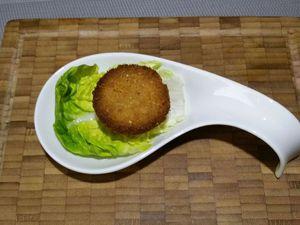 4 - Finaliser la recette en déposant sur un plat de votre choix une demi-sphère de biscuits salés, surmontée d'une demi-sphère de cheese saumon/gambas, et décorer le tout d'une feuille de salade et de gambas entières.