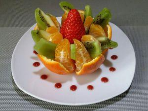 2 - Peler un kiwi, le découper en quartiers puis en lamelles moyennes. Placer la mandarine sur une assiette à dessert et intercaler 1 lamelle de kiwi entre chaque quartier. Déposer au centre du fruit une belle fraise équeutée.  Décorer tout le tour de l'assiette de points de coulis de fruits rouges.