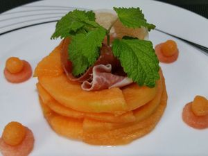 """3 - Sur une assiette de service, disposer les tranches de melon en les superposant en forme de cercle. Placer les 2 tranches de jambon de Parme chiffonnées au centre et le brin de mélisse. Décorer le tour de l'assiette en réalisant à l'emporte-pièce de petits disques de pastèque sur lesquels vous déposerez des billes de melon réalisées à l'aide d'une petite cuillère à pomme (achetée sur le site """"meilleur du chef"""" réf. diam 1,3 cm). Remplir les pipettes du caramel au Porto et les coincer au centre de votre fleur."""