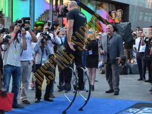 Vin Diesel, perché sur des échasses afin d'être dans la peau de son personnage Groot, reçoit un dessin d'un de ses fans et salut son public.