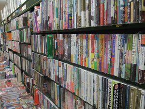 """Et enfin, dans une autre boutique, ces magnifiques étagères de mangas qui se succèdent les unes aux autres... Il y en a pour tous les goûts, et, même si je n'en connais que très peu dans le tas par rapport à tout ce qui était proposé, mes compagnons n'ont pas dû en relever énormément plus. Et tout au fond, comme on le voit sur la seconde photo, de gros guides pour quelques jeux vidéos populaires (des pavés magnifiques en japonais pour un prix assez dérisoire), avec juste au-dessus quelques artbooks (au moins trois fois moins épais pour un prix au minimum doublé~. Mais y'a de beaux dessins. Enfin, je suppose, car dans ce genre de magasins, la plupart des livres sont sous cellophane afin qu'on ne les lise pas sur place). Et pour finir, une photo d'un dernier rayon très """"rose"""", à savoir les mangas pour filles (pays sexiste ? Mais noooon), principalement des Shoujo (""""mangas pour filles"""", de la romance avec un style graphique... à paillettes, disons) et des Yaoi (heu... aussi pour filles, mais axés sur une relation amoureuse entre deux hommes... 'Y paraît que ça plaît à la gente féminine ici)."""