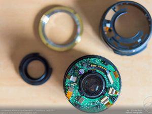 Vues de dessus de l'objectif sans la bague de fixation. On aperçoit les premiers composants électroniques : alimentation et gestion de l'AF ainsi que la lentille arrière au centre.