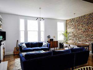 Mur de briques et canapé en velours bleu nuit