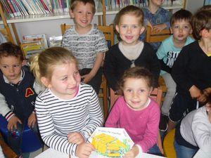 A la bibliothèque d'Etrelles, les enfants présentent leur livre à Franciane.
