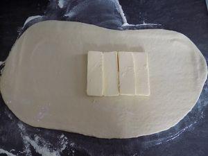 Etaler au rouleau en forme de rectangle, mettre le beurre au centre et ramener les bords sur le beurre comme une enveloppe