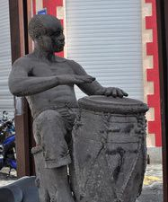 "Gwoka was born in a dark period of the Guadeloupe history . It is not only a music but everything that revolves around it : the dance, games , jokes , a certain way of being, in a word, a whole way of life that comes from our African ancestors. Further down the street, A statue of Marcel Lollia called ""Vélo"" playing the Ka was erected in his honor. When Marcel Lollia died June 5, 1984. His death marks its entry into the History of Guadeloupe, as it becomes a reference in the Gwo Ka music."