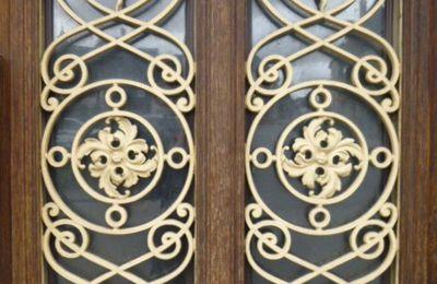 Grille de porte d'entrée donnant sur une place dans une petite ville de l'Eure