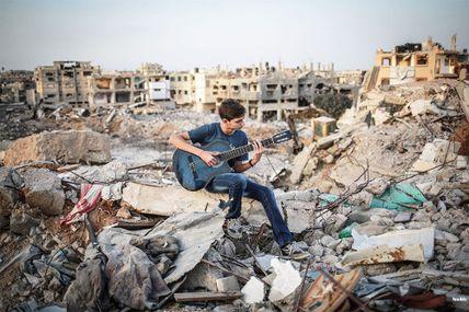 Un jeune palestinien joue de la guitare sur les ruines de sa maison, à Gaza