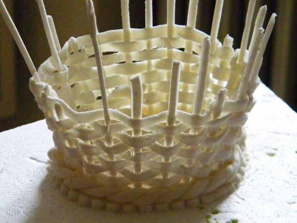 Quand le tressage est terminé, réaliser des boudins en pâte à fleurs et fabriquer une tresse à 2 brins qui sera collée au bas du panier avec un peu de pâte à fleur ramollie quelques secondes au micro-onde ou avec de la glace royale) - Avec des brins du diamètre des tiges/supports, laisser durcir puis remplacer les tiges supports par les boudins. Couper les tiges au niveau de la tresse du panier et les fixer discrètement au tressage, par l'intérieur, avec une pointe de glace royale ou de pâte à fleur ramollie.