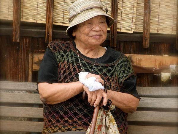 Une OBAATCHAN (grand-mère) pittorèsque qui, elle non plus, n'a pas oublié sa petite serviette éponge pliée afin d'absorber la sueur de son front par ces températures encore chaudes et humides