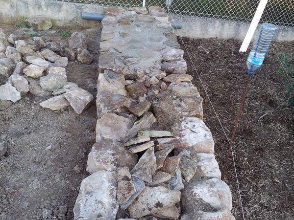 Réalisation d'un muret en pierres pour finir la berge du bassin