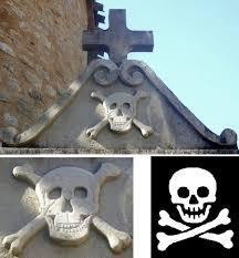 """1/2/3/4/ Les tibias croisés et le crâne sont des symboles occultes usités par le Graal Noir. 5/ Les jambes croisés sur le gisant sont une évocation de la croix kabbalistique """" Tau"""", le X que l'on trouve sur les armes des Bolton."""