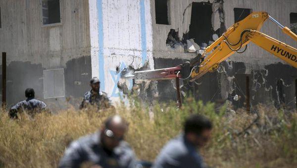 Detruado sub alta sekureco de du konstruataj domoj en Beit-El post decido de la israela Ĉefkortumo, la 29an de julio 2015. REUTERS/Baz Ratner.