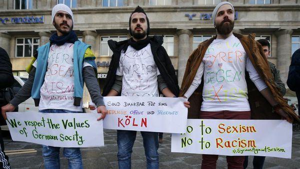 Foto: Siriaj rifuĝintoj antaŭ la ĉefa stacidomo de Kolonjo, scenejo de la seksagresoj, kiuj okazis dum la Novjara nokto, la 16an de januaro 2016. REUTERS/Wolfgang Rattay