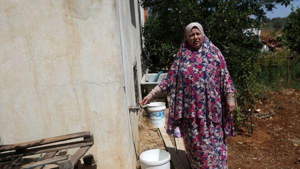 Fatma Ali, montras la fonton de sia ĝardeno, el kio akvo ne defluas, en la vilaĝo Salfit (Norde de Cisjordanio), la 23an de junio 2016. afp.com/JAAFAR ASHTIYEH