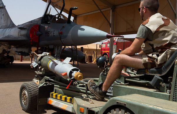 """Photo : (c) EMA / Armée de l'Air - Des """"pétafs"""" montent deux GBU-12 sur un Mirage 2000C."""