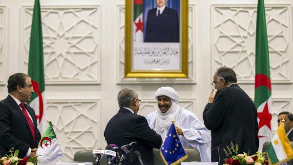 Le ministre algérien des Affaires étrangères Ramtane Lamamra félicite Bilal Agh Cherif, le secrétaire général de la CMA après la signature du projet d'accord de paix, le 14 mai 2015.