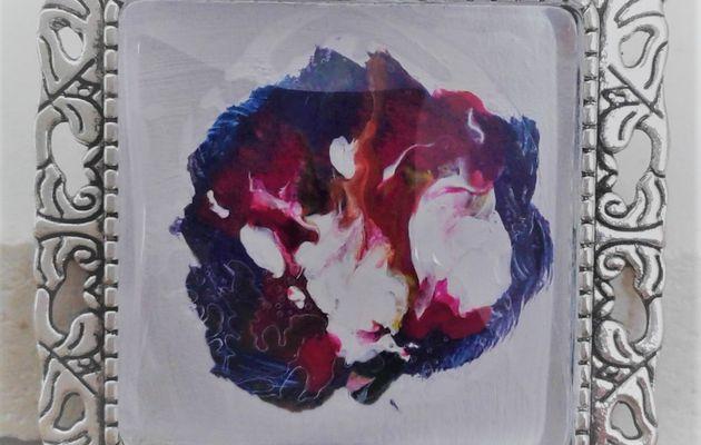 20 euros la broche mini toile peinte sur bijou carré 25x25 mm, blanc, rose, rouge, parme, mauve, bleu, fushia, création française, pièce unique, oeuvre originale LACIK, l'atelier créatif d'isabelle krief pour france handi art.  J'ai préparé le fond blanc pour peindre cette petite toile directement sur le bijou. Puis, avec les couleurs primaires, bleu, rouge, jaune, j'ai obtenu des volutes de parme, rose, fushia, violine, la patine est blanche. J'utilise de la peinture acrylique et du vernis laque de peintre, tout est à l'eau, sans danger et la broche est en métal argenté vieilli, sans nickel.  Cette broche est aussi un pendentif, voir au dos, il y a les 2 systèmes d'accroche.  La broche accessoirise tout type de vêtement, même les pantalons, accrocher une broche au bas d'un jean, ça donne un effet bluffant, sur un sac aussi, une écharpe, un snood, une casquette, la broche, l'accessoire indispensable.
