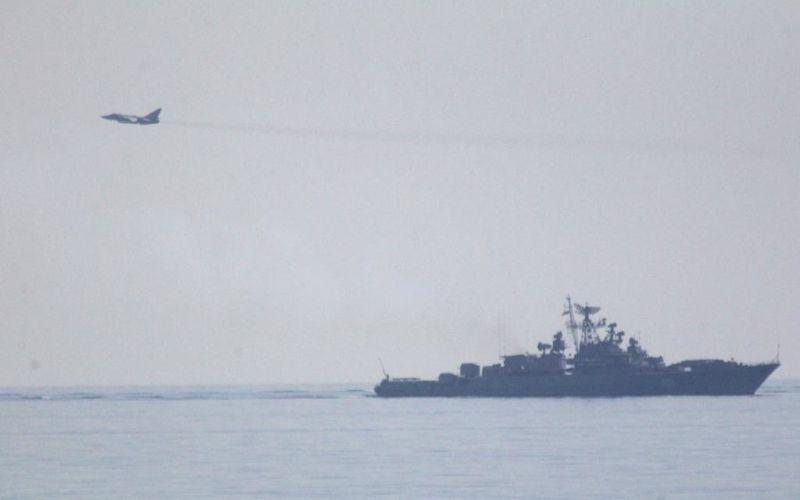 Un Su-24 russe effectue des passages bas autour d'un navire de l'US Navy