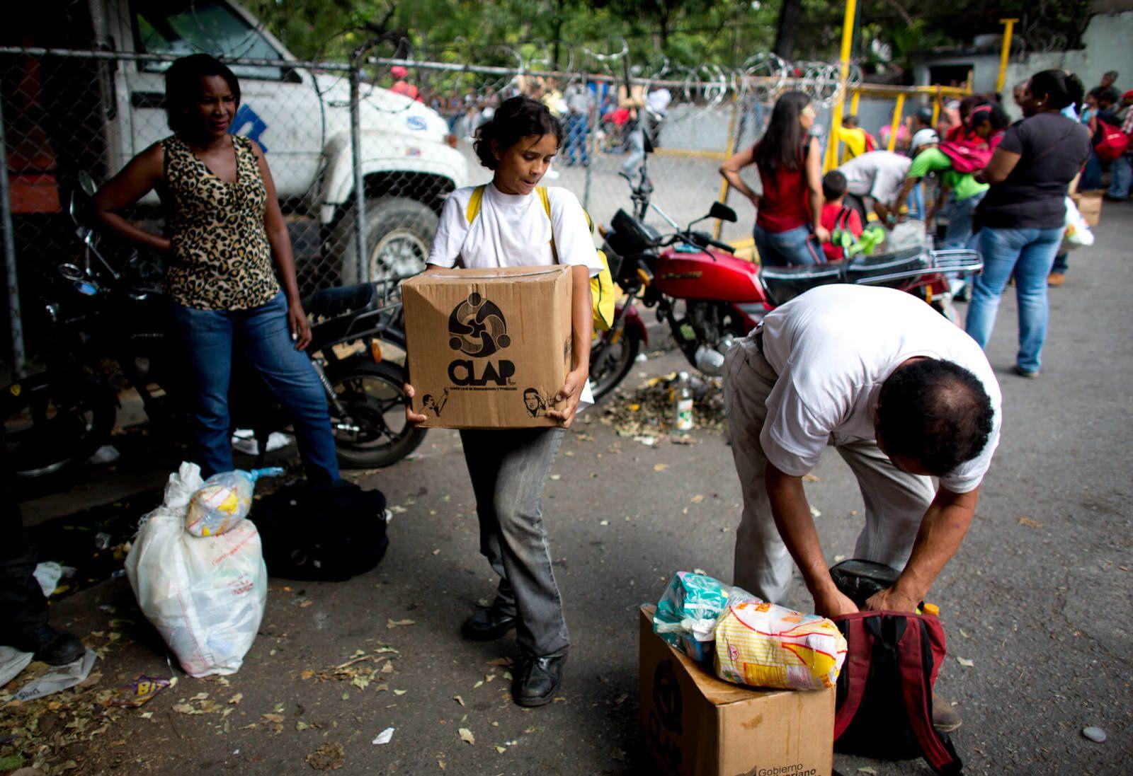"""Les gens prennent des boîtes d'aliments de base, comme les haricots, le riz, le thon et le lait en poudre, fournis par le programme gouvernemental """"CLAP"""", qui représente les Comités locaux d'approvisionnement et de production, à Caracas, Venezuela, le 16 mai 2018. Le resserrement des sanctions financières par l'administration Trump étouffe le gouvernement affamé de liquidités alors qu'il s'efforce de nourrir sa population. Ariana Cubillos / AP"""