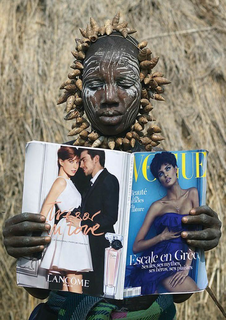 A Mursi tribe woman discovers Vogue magazine, Ethiopia.