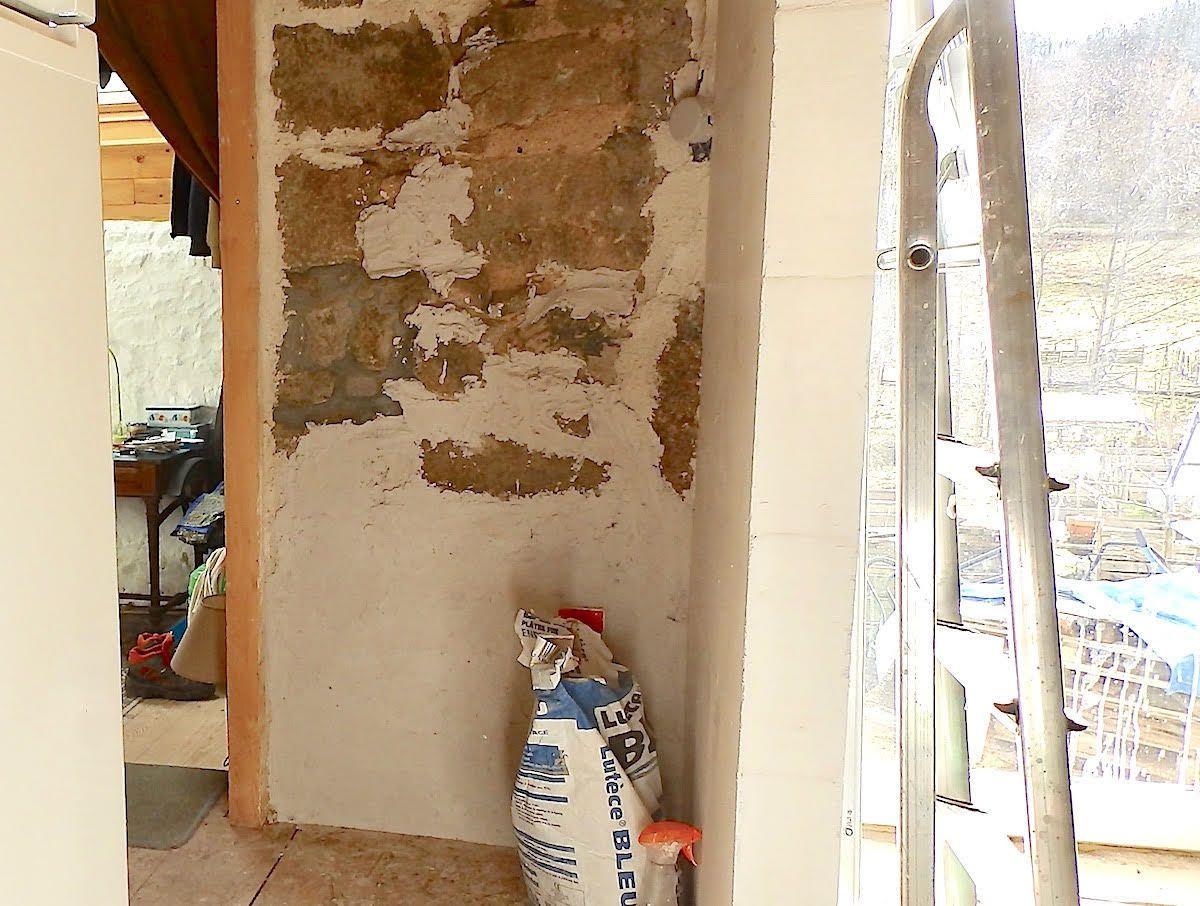 Enduire le mur de pierre derrière le frigo.