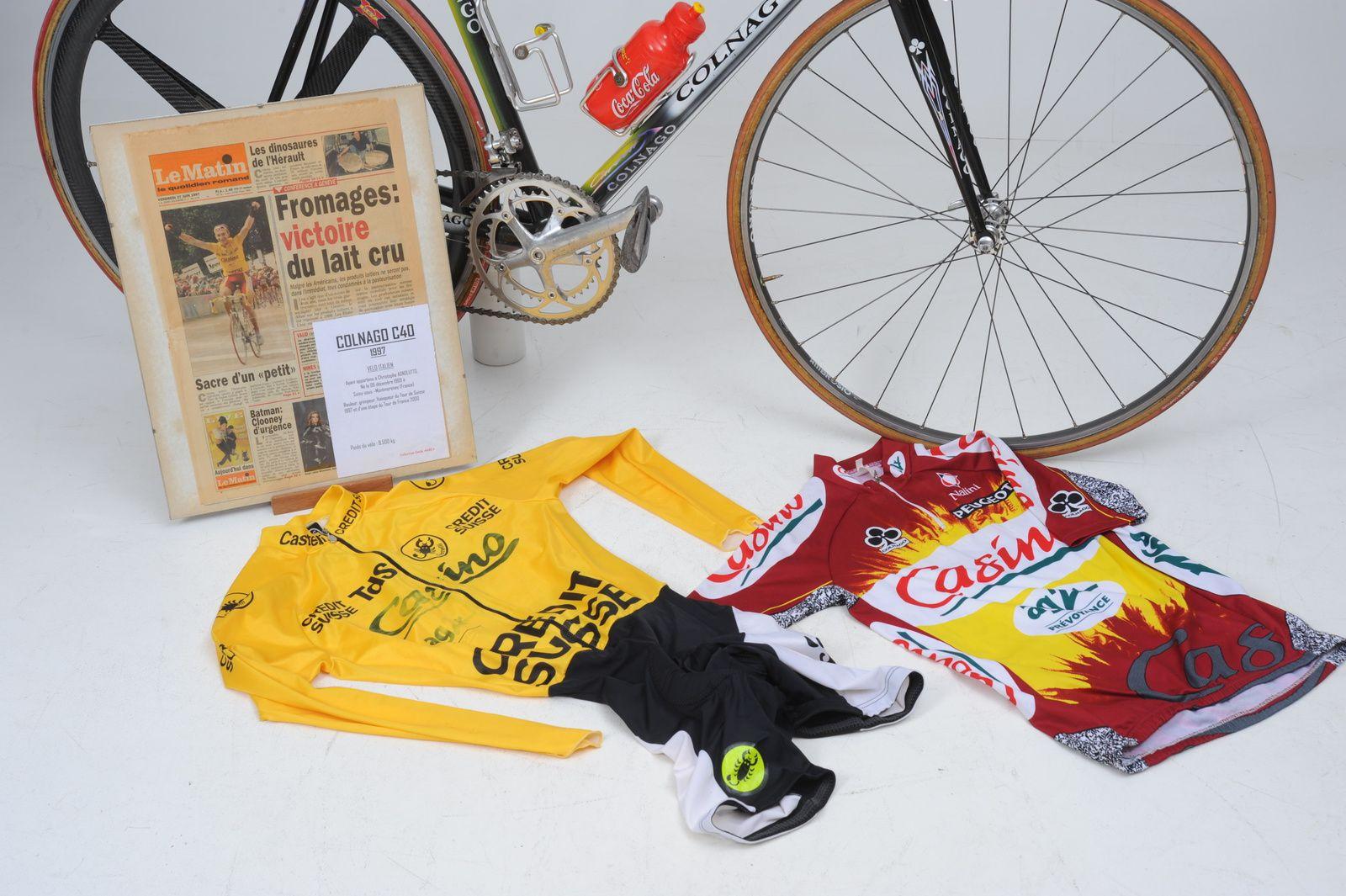 Le vélo avec le présentoir et les tenues (maillot Casino et combinaison jaune du Tour de Suisse).