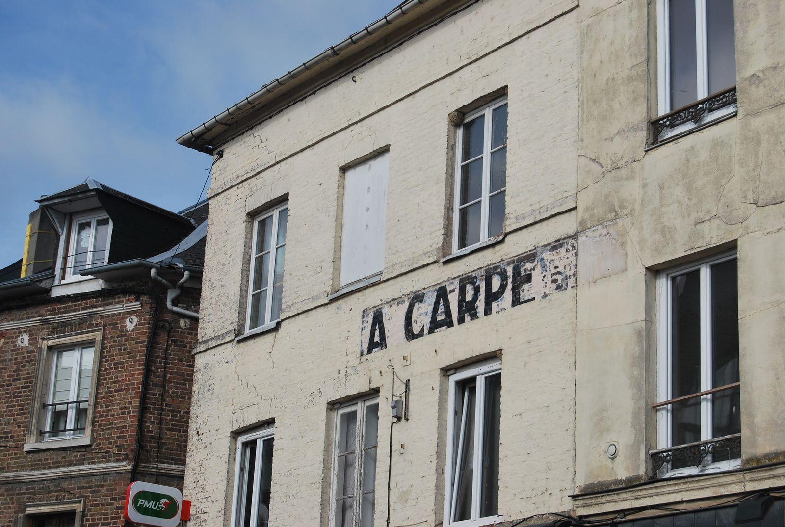 """L'hôtel de la Carpe sur une photographie des années 1970. A noter, l'effacement du mot """"hôtel"""" sur l'enseigne. Sur le deuxième document, le même lieu photographié en juillet 2019 (cliché Armand Launay)."""