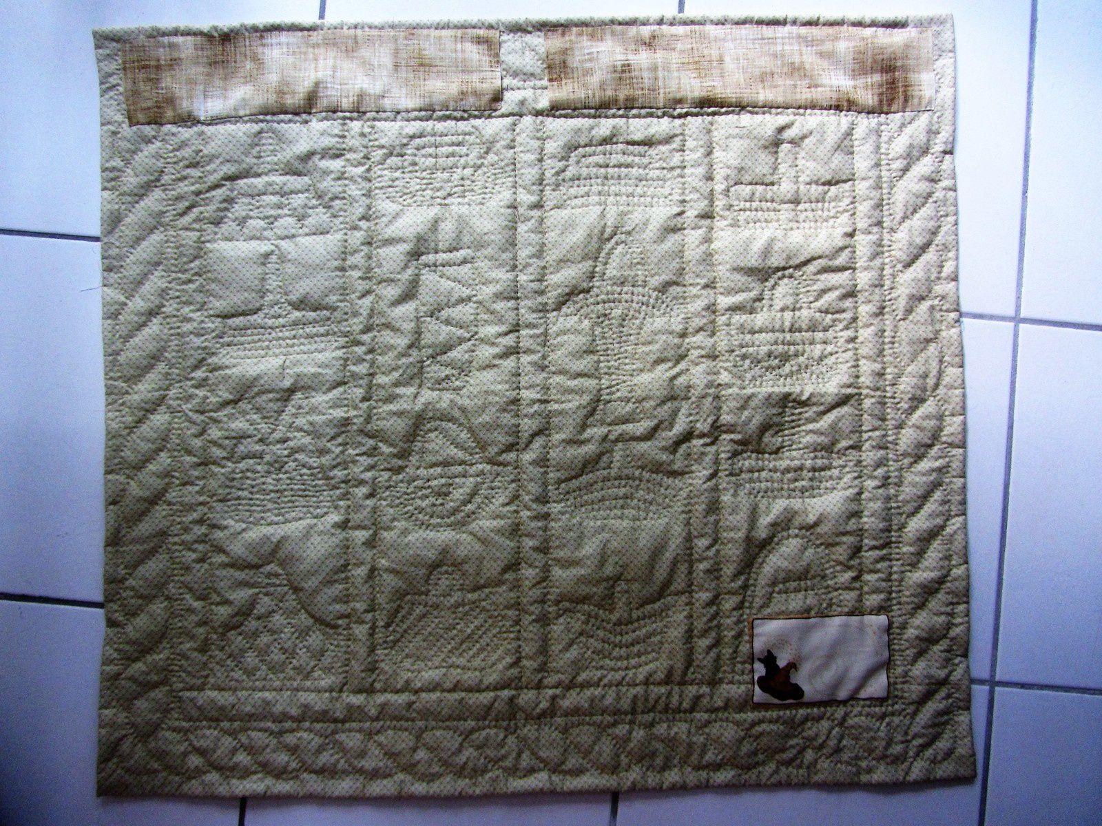 Et voici le dos du panneau quilté, avec son étiquette et les manchons pour l'accrocher.