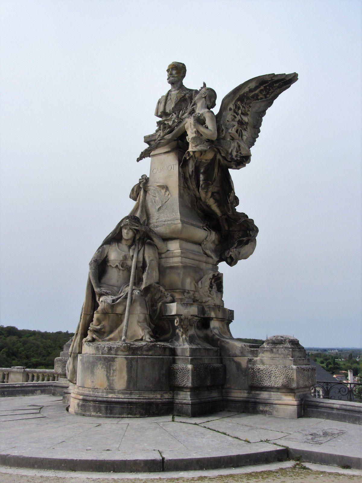 Au sommet le buste de Sadi Carnot, à mi-hauteur, une Renommée, ailes déployées, dépose une palme et une branche d'olivier