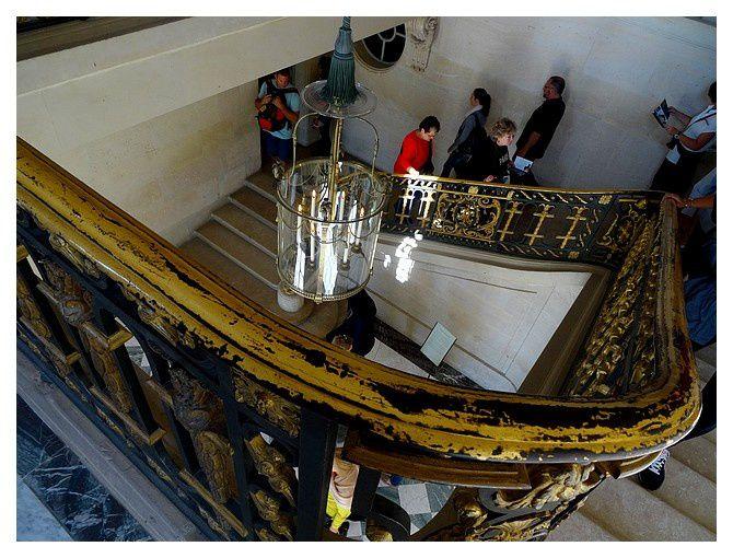 l'escalier d'honneur du château, tournant à deux volées droites, construit en pierre calcaire de Saint-Leu et orné d'une rampe en bronze doré et fer forgé, œuvre des serruriers Louis Gamain et François Brochois. Son dessin est ample et scandé de médaillons ovales à tête de coq, qui portaient à l'origine le chiffre de Louis XV, remplacé ensuite par celui de Marie-Antoinette, les lettres M et A entrelacées.