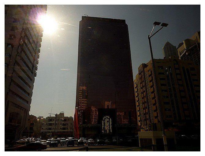 gratte ciel en contre jour , et sur la facade de verre, reflet des immeubles en face